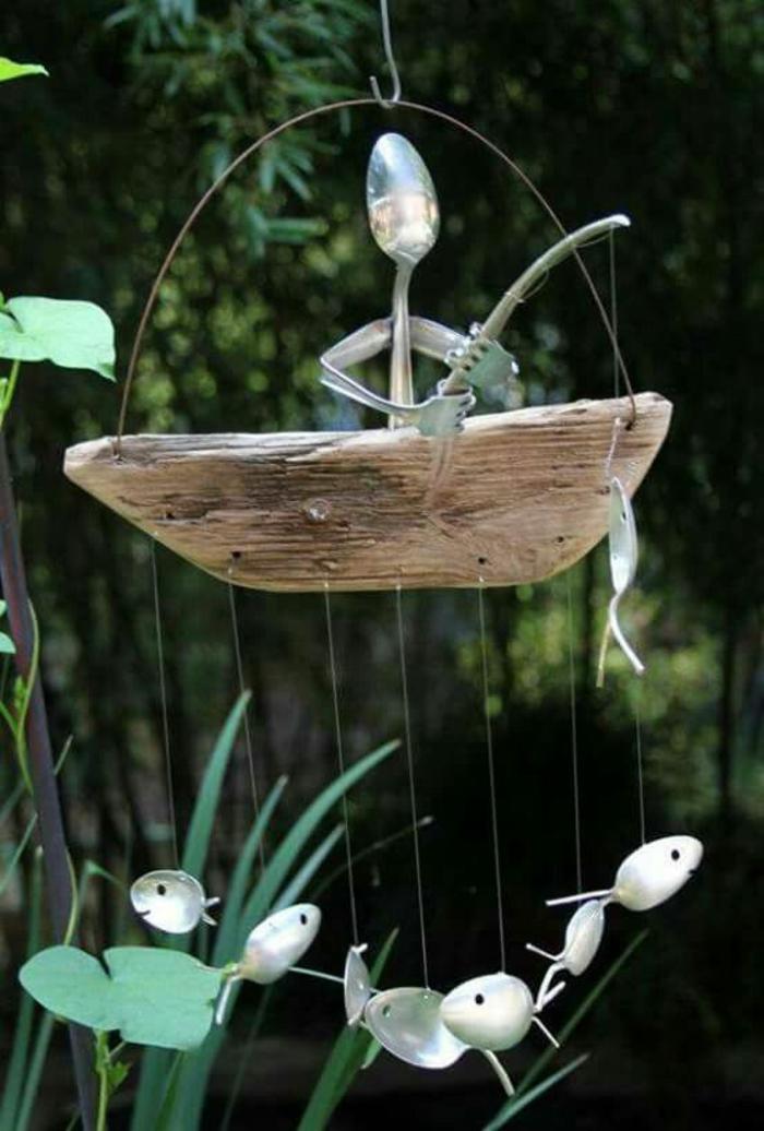 composition décorative avec des cuillères, pêcheur avec des poissons qui flottent dans l'air avec des petites cordes transparentes, decorer son jardin