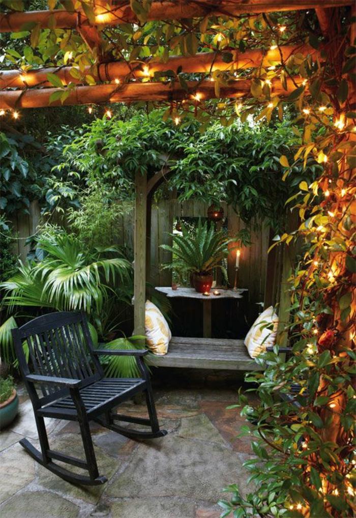 idee amenagement jardin devant maison, chaise basculante noire en bois, pergola avec des plantes vertes, ambiance cool relaxante