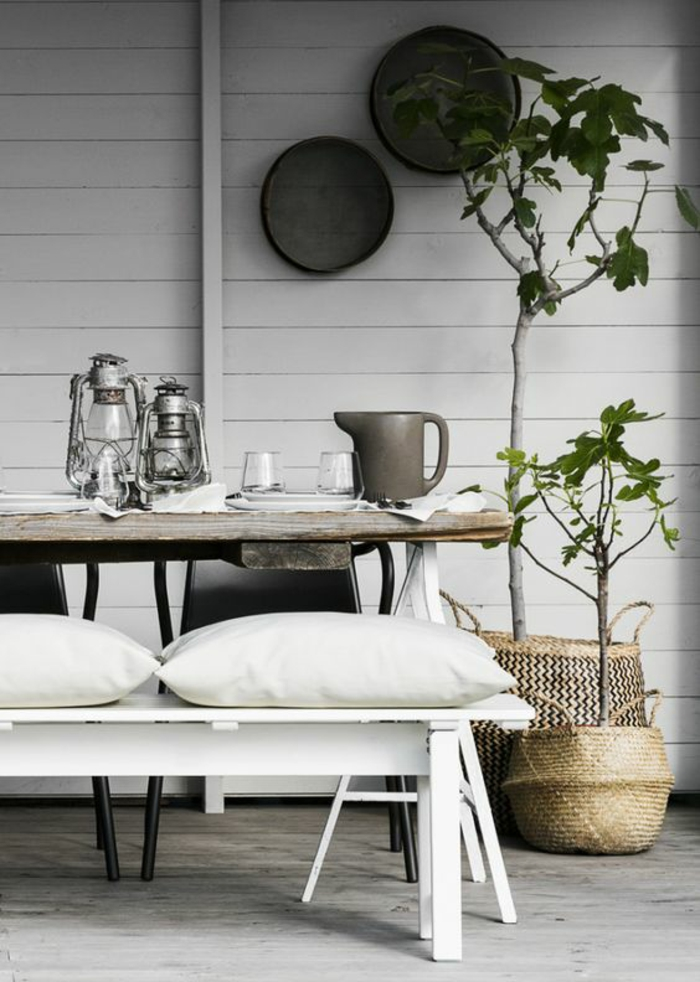 amenagement exterieur, entrée d'une maison, decorer son jardin avec un banc blanc et des plats noirs sur le mur de la maison,deux lanternes en couleur grise, coin zen