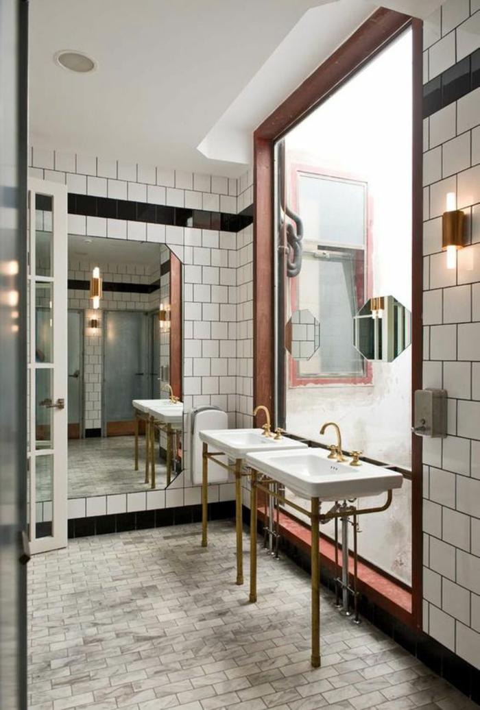 salle de bains avec des murs recouverts de carrelages blancs, carrelages du sol en gris, grand miroir carré bien illuminé, deux lavabos vintage avec des tubes et des éviers en couleur or, habiller un mur en carrelages