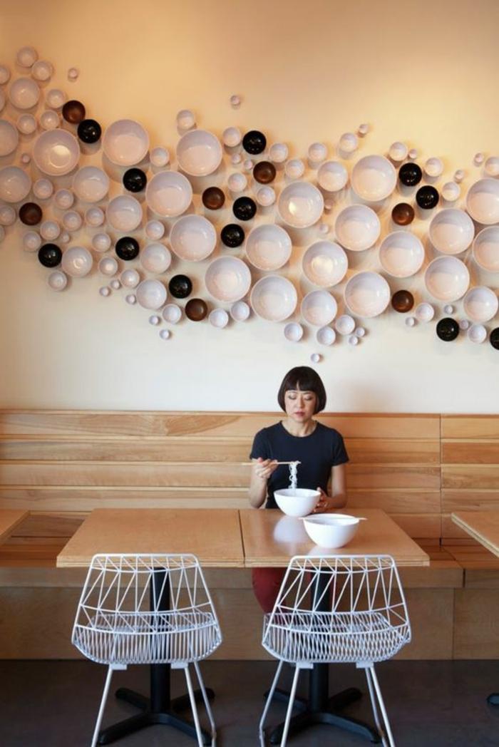 decoration murale design, plats blancs et noirs, petits et grands, deco mur cuisine, deco murale, ambiance ludique, mur peint en ivoire, a moitié revêtu de bois PVC nuances marron et beige, deux chaises design en métal blanc