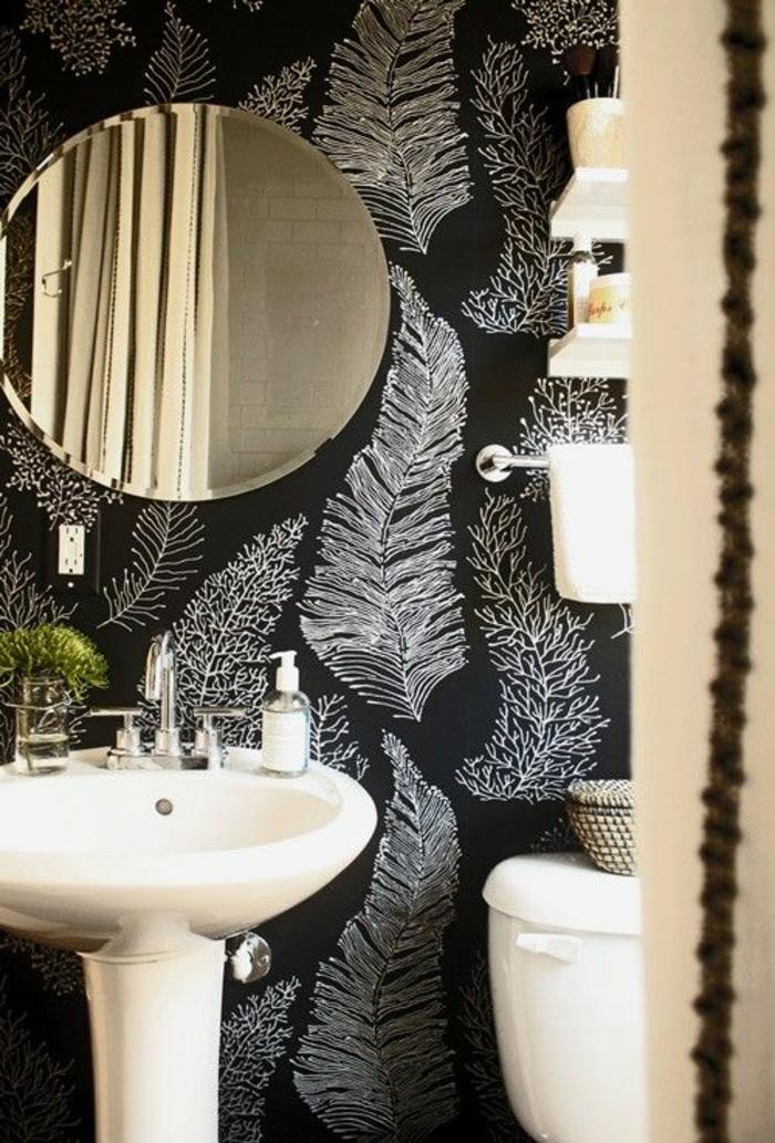 decoration murale design avec un papier peint en noir et blanc aux motifs plumes, grand miroir rond aux bords métal couleur or, lavabo blanc en forme ovale