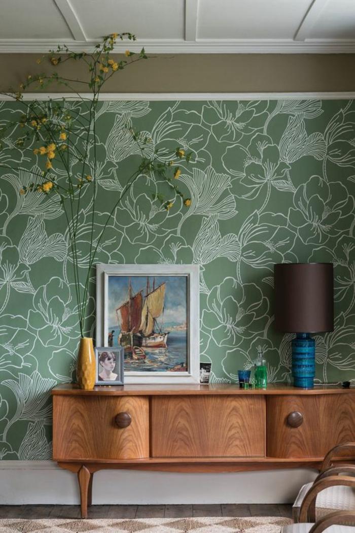 décoration murale chambre, décoration murale salon, déco murale, papier peint en vert et blanc aux motifs feuilles d'arbres et fleurs, meuble rangement en marron avec deux grandes poignées rondes en bois, partie de mur peinte en réséda, dalles de carrelage aux motifs losanges beiges et marron