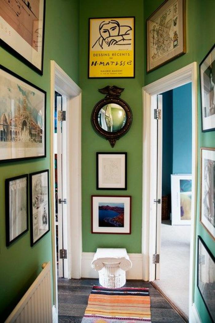 murs peints en vert herbe, idee deco mur, décoration riche avec des tableaux grande taille forme rectangulaire, parquet nuances grises et noires, tapis rectangulaire rayures horizontales oranges, jaunes et noires