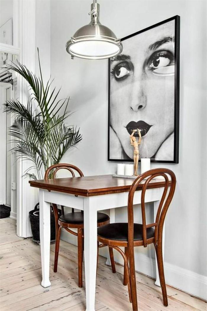 grande photographie en noir et blanc au cadre noir, visage de femme maquillée, luminaire style industriel couleur argent, table carrée au plan couleur cerise et pieds bois blanc, palmier dans un coin, parquet en bois en couleur beige, cadre photo mural