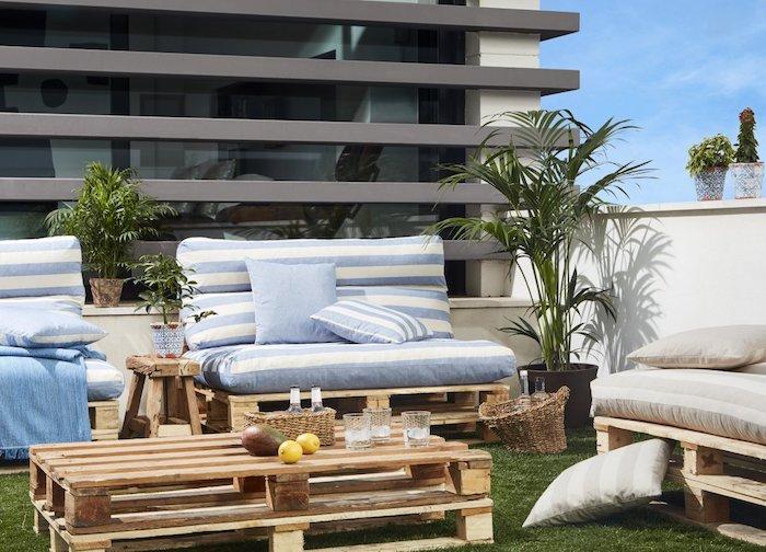 deco terrasse sur toiture, recouverte de gazon, table en palettes superposées, fauteuil en palette, plantes exotiques