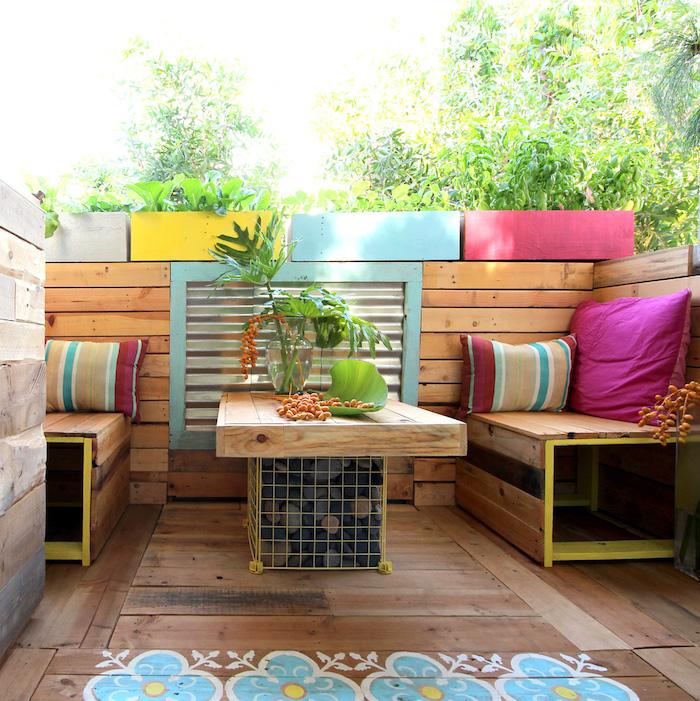 deco terrasse en bois avec une table basse en palette facile gabion et petis banquettes, plantes dans des bacs à fleurs colorées