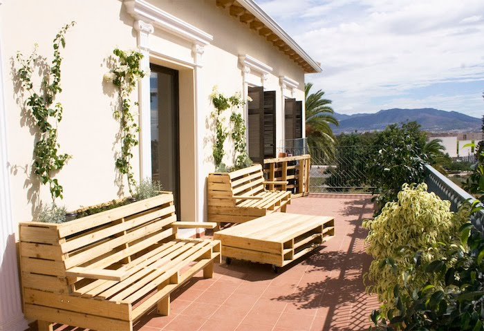 decoration terrasse avec un salon de jardin palette avec banquette palette et table basse bois de palette, sol en carrelage marron