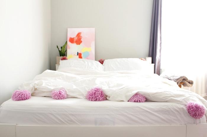 linge de lit blanc décoré de pompons et tete de lit originale en tableau décoratif art abstrait derrière le lit