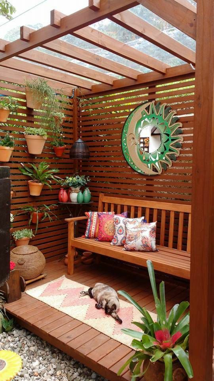 pergola en bois marron, decoration jardin terrasse, balcon fleuri, miroir sorcière moitié lune, moitié soleil, tapis en blanc et rose, mur végétal avec des pots colorés