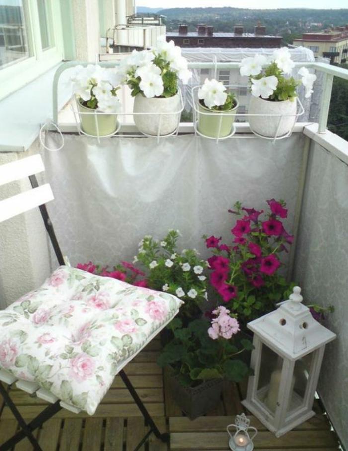 chaise en bois blanc et métal noir, lanterne en métal blanc, pots avec des violettes blanches et fuchsia, amenagement petite terrasse, decoration terrasse exterieur, sol avec lame bois a emboîter