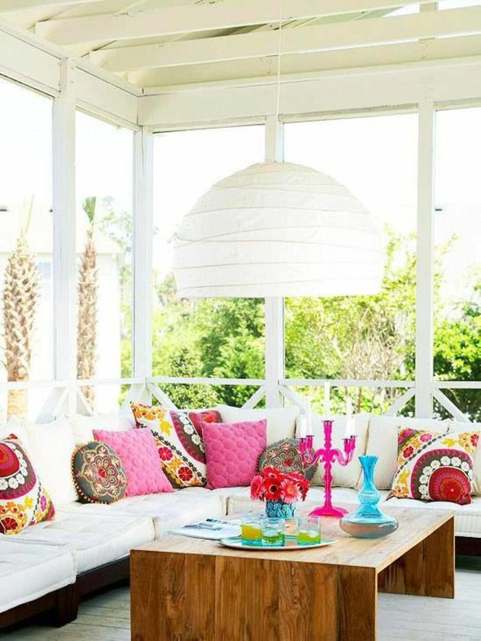 grand luminaire en carton couleur crème, idée déco terrasse, pergola en couleur blanc crème, table basse en bois plusieurs nuances de marron, meuble de jardin en angle avec des coussins blancs
