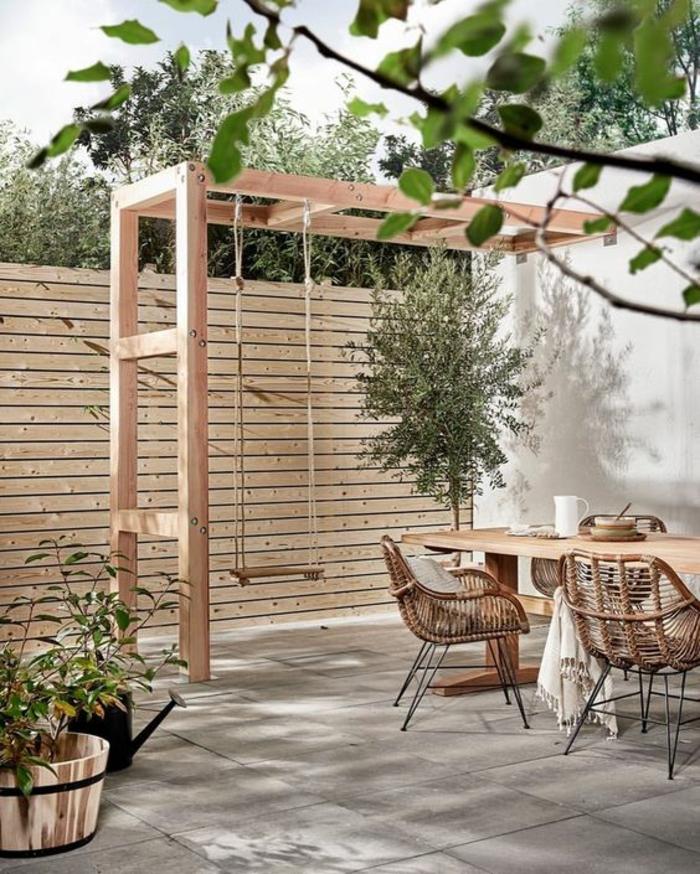pergola bois clair avec balançoire en bois suspendue, decoration terrasse exterieur, chaises en canne tressée et métal noir, dalles gris clair