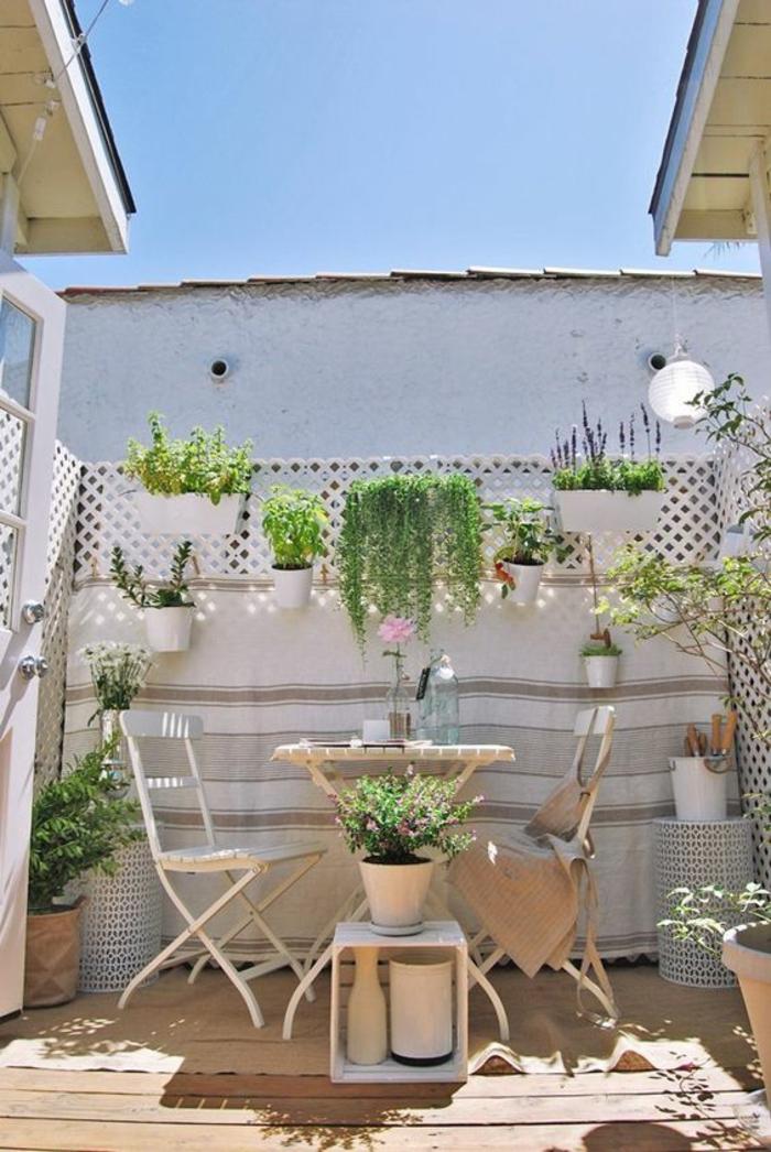 idee deco terrasse en style bohème, balcon fleuri, decoration jardin terrasse, meubles de jardin vintage en métal blanc, sol recouvert de bois clair, mur végétal porte-plante avec des pots blancs