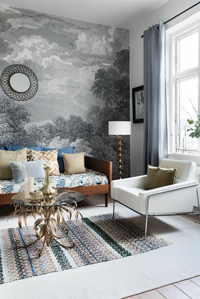 deco photo, un mur en style vintage, papier peint en noir et blanc aux motifs arbres dans une foret, nuages, paysage nature, tapis rectangulaire en nuances pastels, fauteuil blanc large