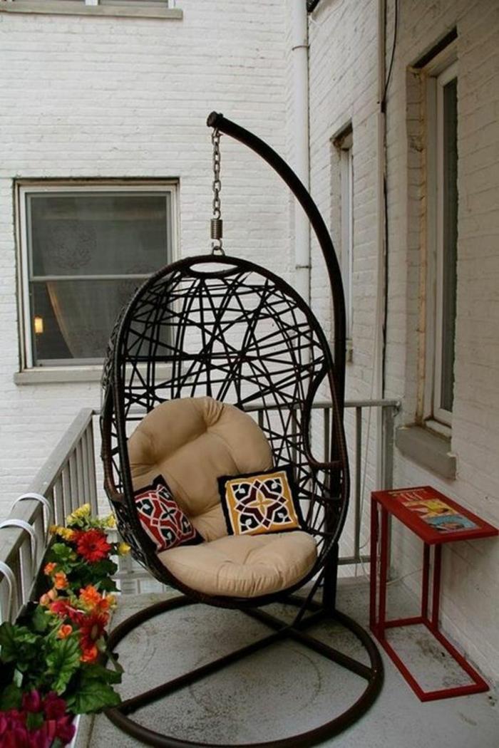 idee amenagement terrasse, amenagement petite terrasse, fauteuil œuf en rotin noir suspendu sur un statif en élément, garde-corps décoré de pots rectangulaires avec des fleurs jaunes et oranges, table en métal rouge en forme rectangulaire étroite