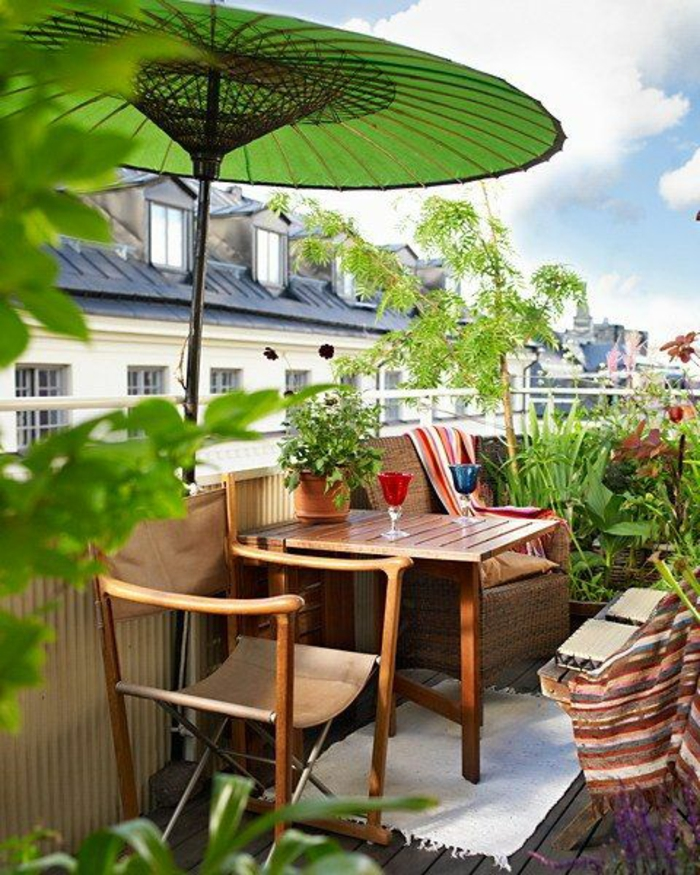 idee deco terrasse,balcon fleuri, grand parasol vert herbe en style chinois, meubles en bois clair avec des chaises en bois et tissu en lin