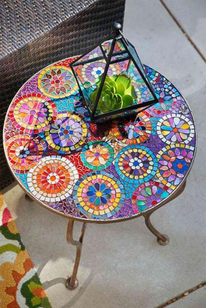 table au mosaïque riche en couleurs vives aux motifs cercles, lanterne en métal et en verre avec une plante cactus dedans, idée pour décorer son jardin ou sa cour