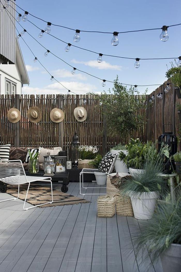 déco jardin récup, guirlande lumineuse avec des ampoules nues, quatre chapeaux accrochés au cintre, canapé et fauteuils de jardin, tapis rectangulaire en beige et vert, deco jardin pas cher