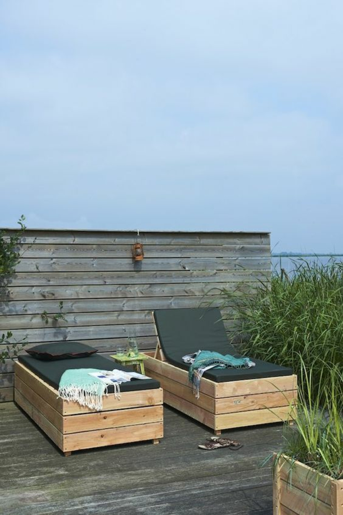 salon de jardin en palette, canapé palette, chaises longue recouvertes de matelas noirs, sol en bois noir foncé, zone relax devant une villa autour d'un lac