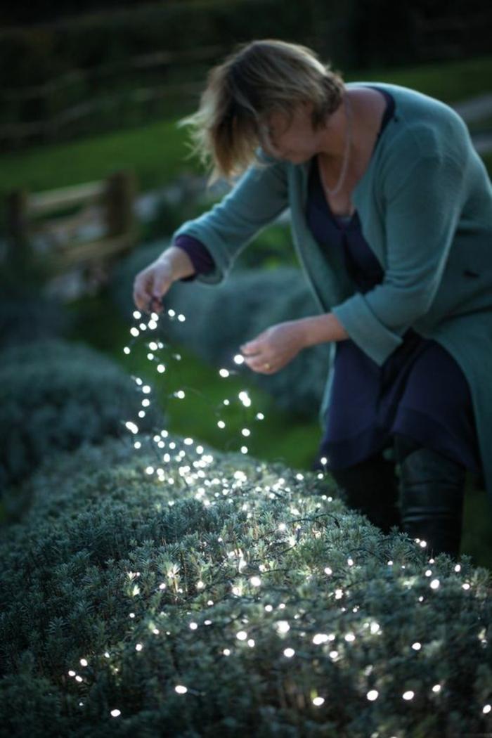 une guirlande lumineuse posée sur les plantes, ambiance magique dans la nuit, accents lumineux, decorer son jardin avec de la lumière