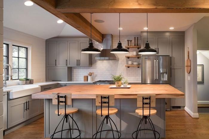 une cuisine grise et bois qui mélange le style champêtre et industriel, équipée d'un îlot central avec comptoir en bois massif illuminé par trois suspensions d'esprit atrelier