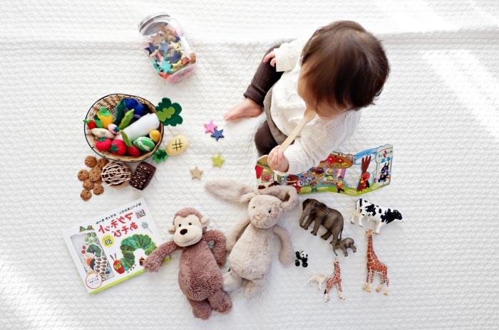 large couverture de lit de nuance blanche avec jouets dans panier ou bocal, comment arranger les jouets petit enfant