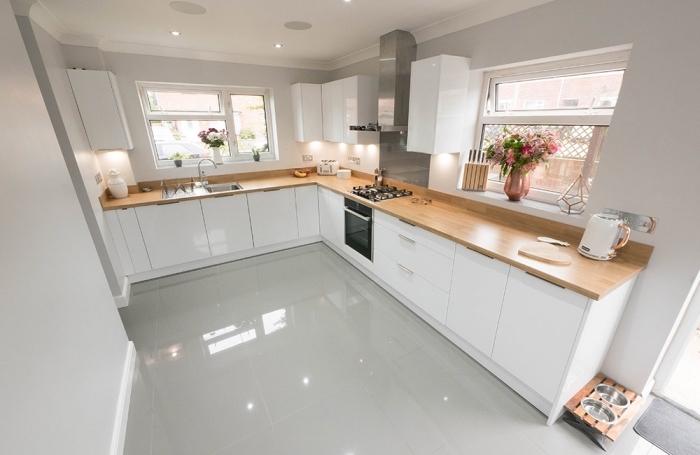 modèle de cuisine blanche laquée aménagée en L avec armoires blancs et plan de travail de bois stratifié clair