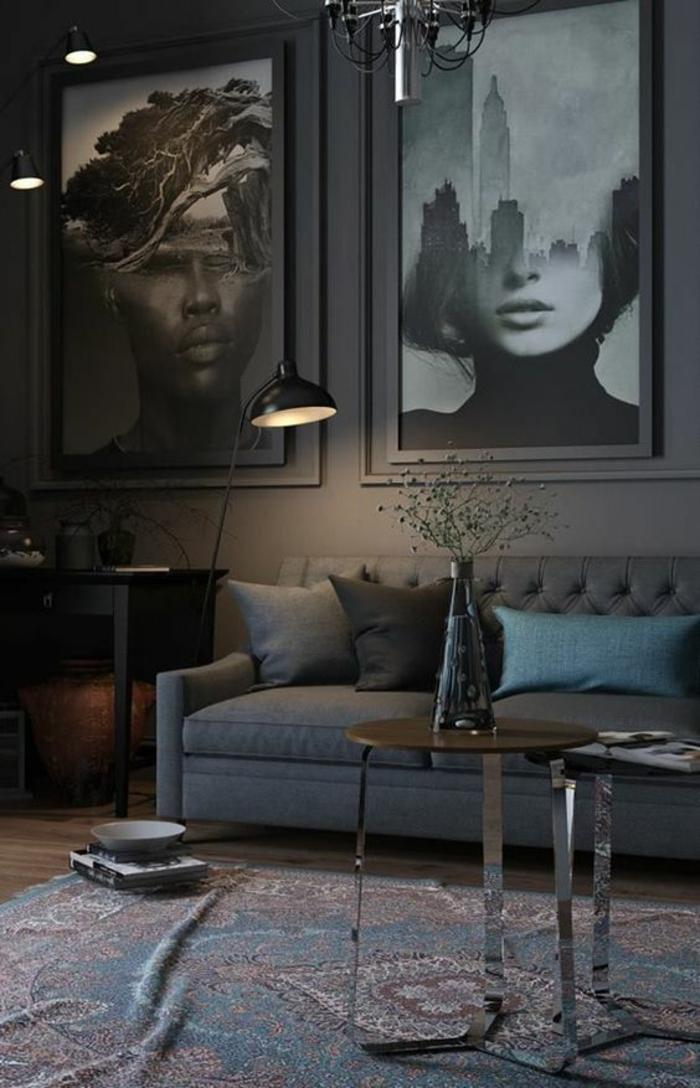 deco murale, idee deco mur, intérieur sombre et mystérieux, lumière discrète d'un luminaire sur pied, canapé en tissu gris clair, coussin bleu pastel, noir et gris, tapis oriental en bleu et blanc, deux photo images avec visage d'homme et visage de femme, a moitié paysages