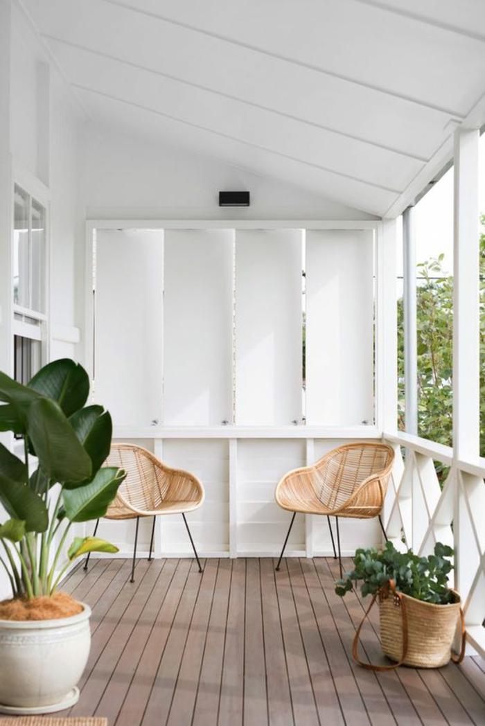 decoration jardin terrasse en style minimaliste, deux fauteuils en canne tressée avec des pieds en métal noir, grand pot de plante blanc, sol recouvert de poutres de bois marron, sac femme transformé en pot avec plante verte