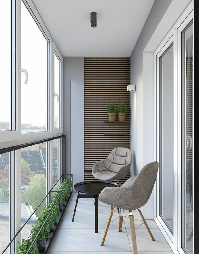 deux fauteuils design en tissu gris avec des pieds en bois clair, petite table ronde en métal noir, idée déco terrasse, mur couvert d'éléments en bois clair, sol en dalles blanches finition matte, plantes vertes tout au long du garde-corps