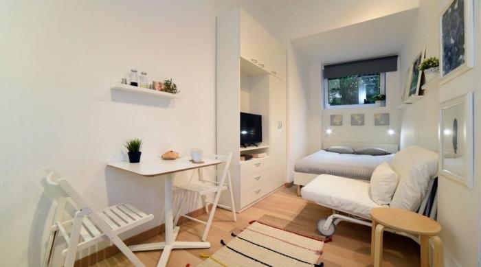 aménager un petit appartement aux murs blancs avec coin intime et table à manger blanche pour bureau