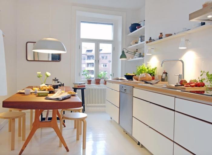 exemple de cuisine blanche aménagée avec table à magner et meubles blancs sans poignées, modèle de rangement vertical