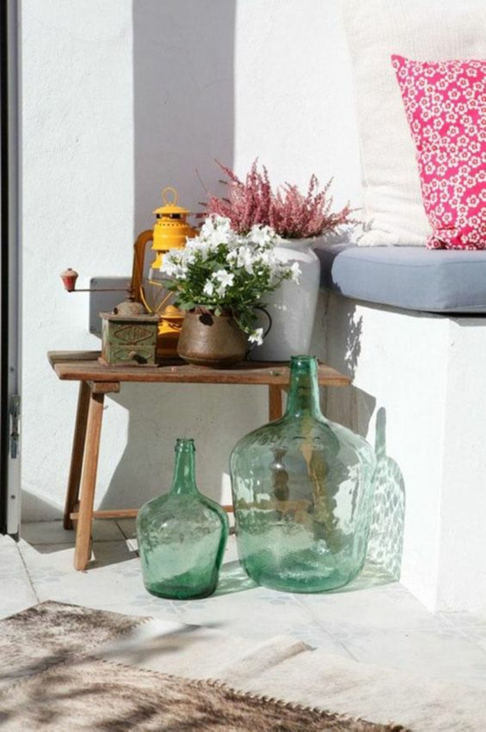 un coin de jardin avec des bouteilles de verre transparent, niche recouverte de coussins gris et fuchsia pour former un canapé, décorer son jardin, aménagement jardin pas cher