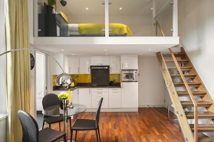 aménagement petit appartement avec coin intime équipé d'un lit mezannine sous plafond et table de chevet noir mate