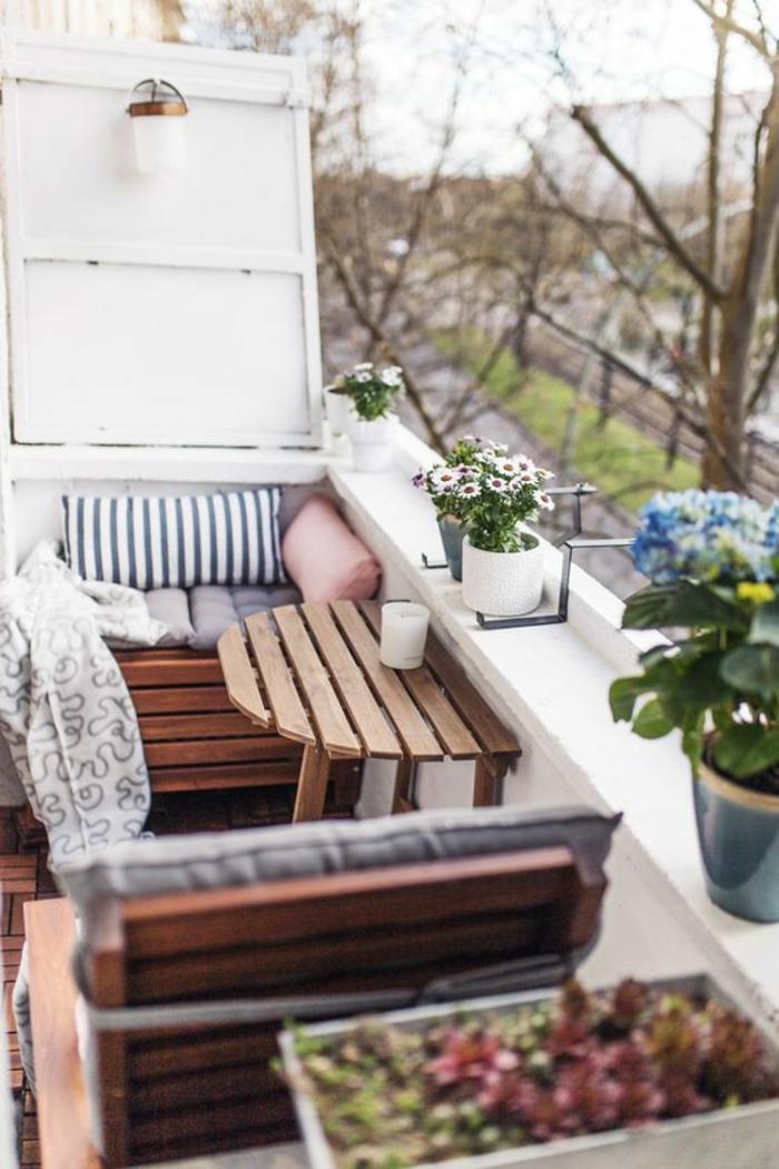 coin de relax extérieur, amenagement petite terrasse avec des meubles en palettes, table palettes pliante sur le garde-corps, pots de fleurs avec des marguerites blanches et bleues