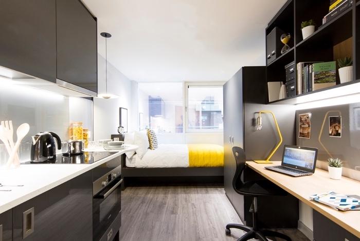 idée aménagement studio étudiant avec petite cuisine en blanc et noir et coin bureau en gris avec plan de travail bois