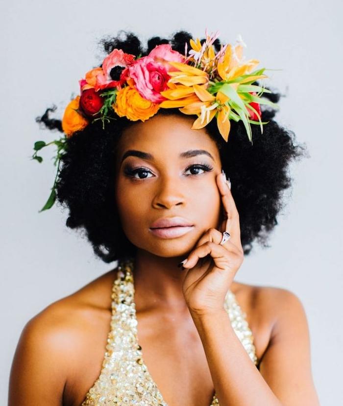 femme afro avec cheveux accessoirisés d une couronne de fleurs colorées, coiffure cheveux crépus exemple et robe de mariée à pailelttes