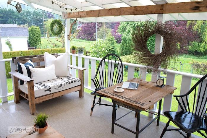 banquette en palette avec coussins noir et blanc et une table en bois et metal, chaises bois noires, terrasse couverte