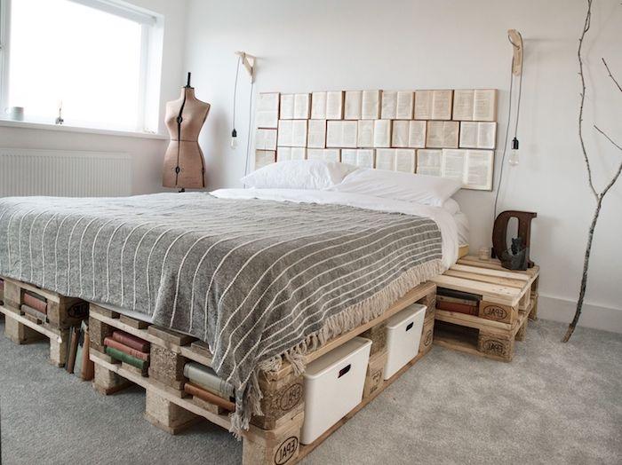 tete de lit originale en livres ouvertes sur un murs blanc, linge de lit gris et blanc, lit en palettes avec des rangements livres intégrés, tapis gris, murs blancs