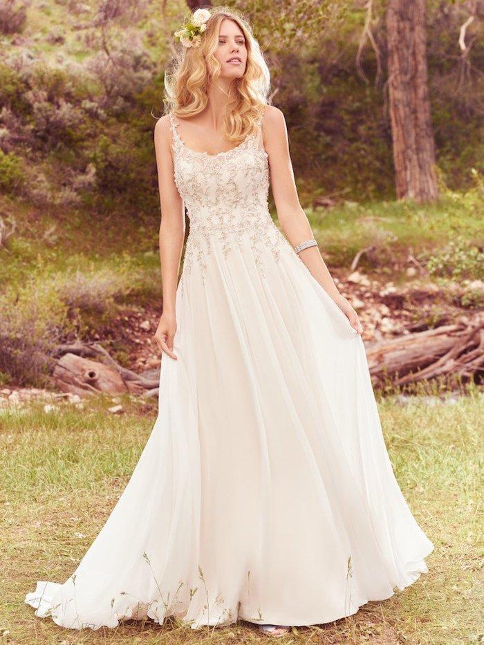 robe de mariée champetre avec une jupe coupe empire, top à broderies argent, coiffure boucles mariage avec des fleurs dans le cheveux