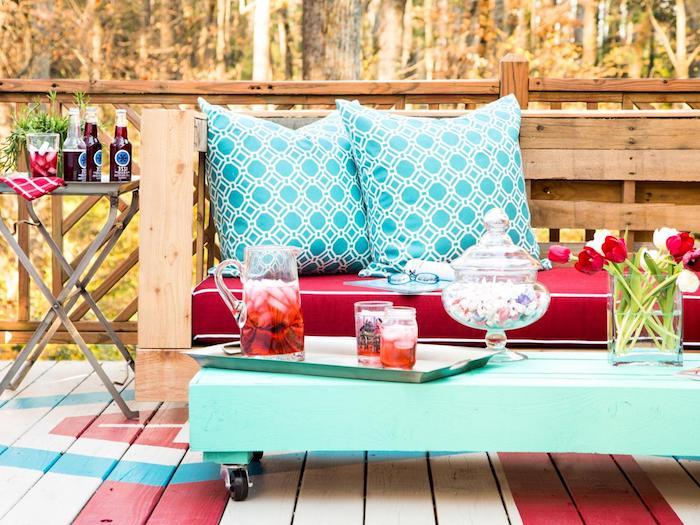 exemple de salon de jardin en palette avec un canapé bois avec coussin d assise rouge, coussins décoratifs bleus et une table basse en palette repeinte en bleu à roulettes, deco terrasse