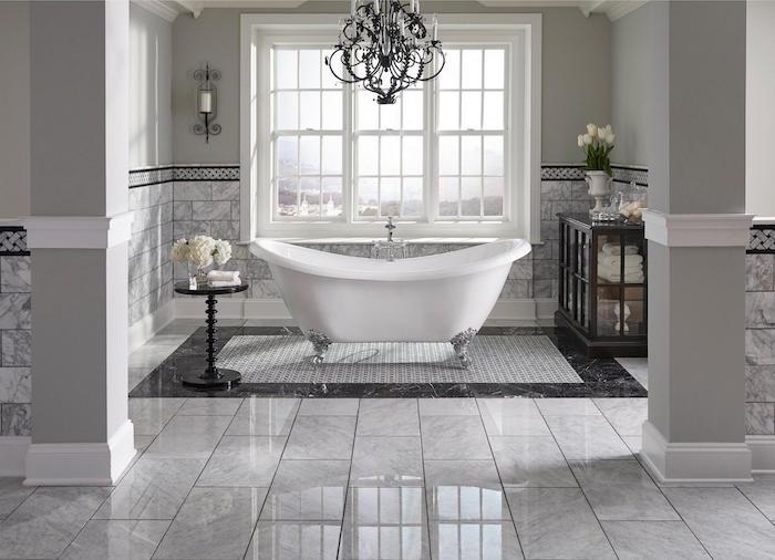 grande sdb de luxe avec sol en carrelage brillant gris marbre et baignoire ilot type retro