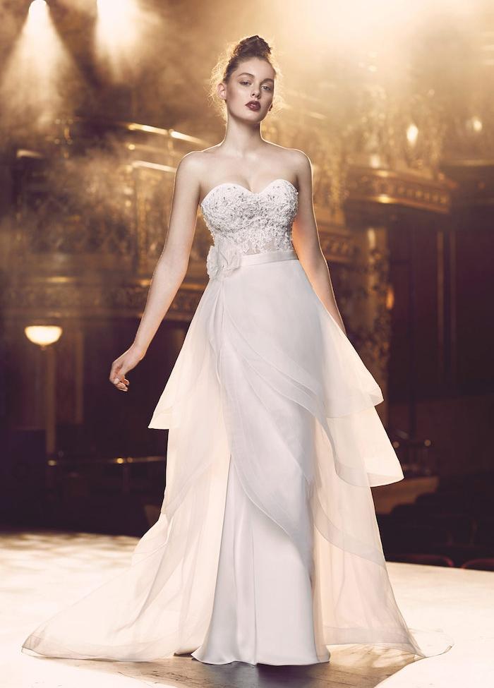 robe de mariée coupe droite avec des voiles de coté et un bustier décoré de pierres, ceinture avec fleur