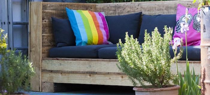 coussin salon de jardin palette bleu marine sur une banquette en palette décorée de coussins décoratifs colorés dans un jardin