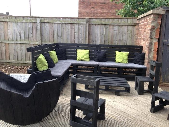 meubles de jardin en palettes constitués de canapé en palette noir, table basse en palette et petites chaises, fauteuil touret de bois