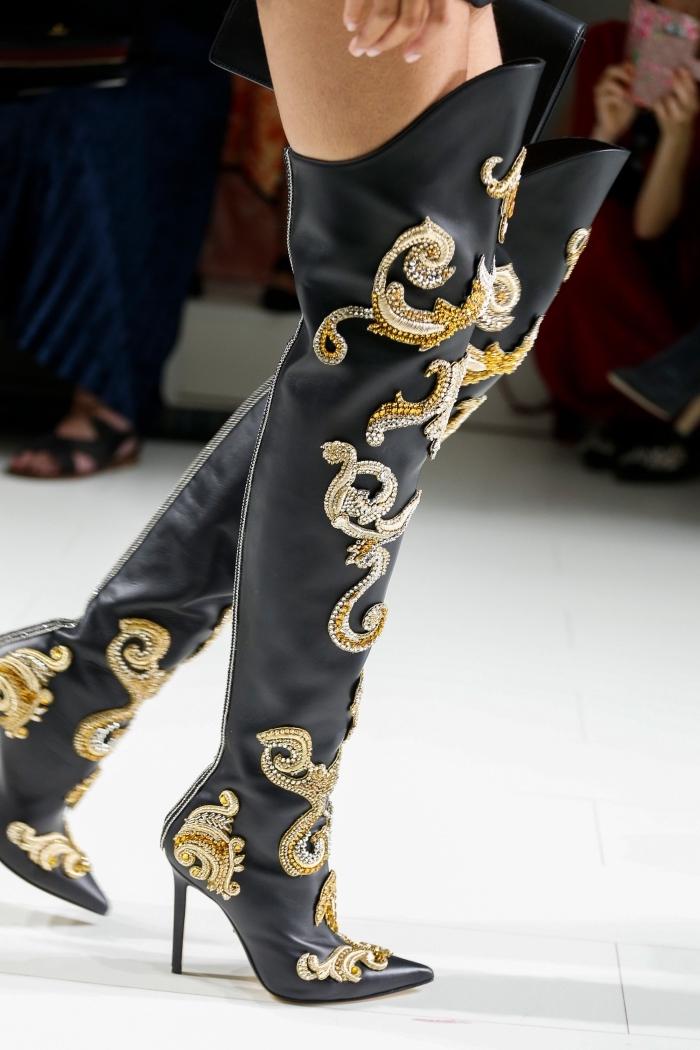 modèle de bottins à longueur au-dessus des genoux à design cuir noir avec décoration en or et argent de la collection de Versace
