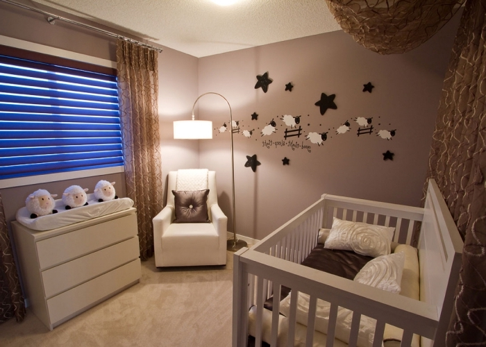 modèle de chambre bébé aux murs beige et plafond blanc aménagée avec meubles de bois peint en blanc