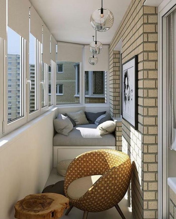 aménagement de terrasse en longueur, idee deco terrasse en style élégant, murs en briques ivoire, fauteuil d'angle deux places matelas gris, coussins gris, blanc et bleu marine, fauteuil coque en rotin tressé, table en forme de tronc d'arbre en style rustique