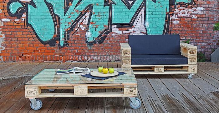 meuble avec palette en bois, table basse palette à roulettes et canapé en bois avec coussin d assise noire, mur en graffiti